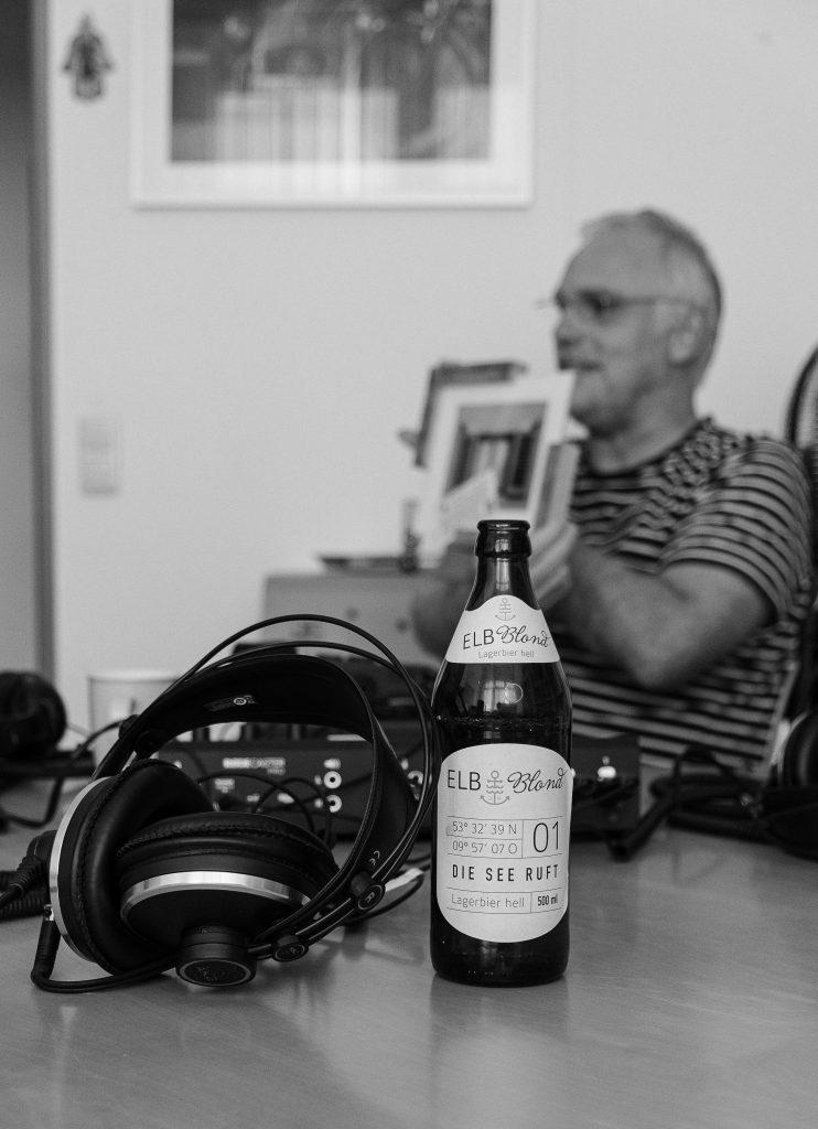 Bierflasche aus Harburger Brauerei im Vordergrund - unscharf im Hintergrund Christoph mit Bild in der Hand